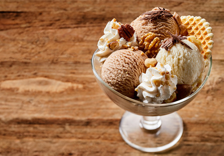 Glass bowl of ice cream dessert with chocolate, nuts and waffle, from above close-up on wooden background with copy space