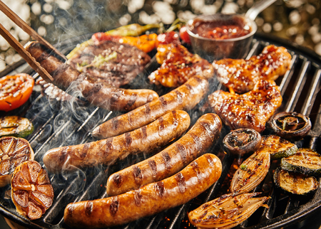 Tasty summer picnic with grilling food sizzling over the hot coals on a BBQ including steak, sausages, chicken and assorted vegetables Stock Photo