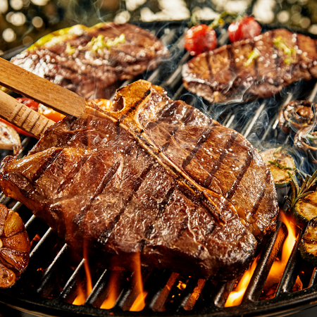 Tasty marinated t-bone steak barbecuing on a fire amongst assorted meats, garlic, onion, and tomato at a summer BBQ