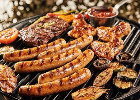 Heerlijke zomer BBQ grillen over het vuur met worstjes, kippenvleugels, biefstuk, champignons, tomaat, babymerg, knoflook en ui