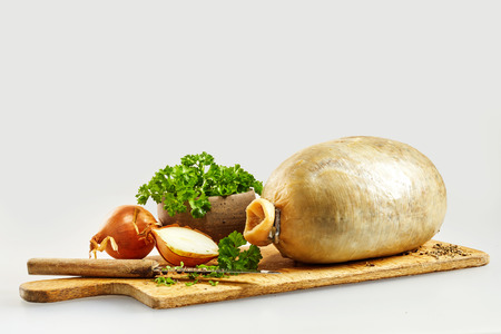 neeps: Preparing a traditional Scottish haggis with a sheep stomach filled with the minced offal, suet, oatmeal, seasoning and onion on a wooden board with ingredients and copy space