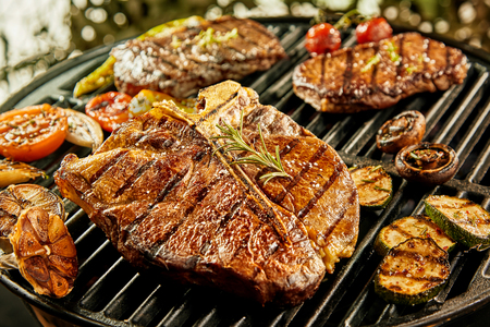 foreground focus: Selection of meat and vegetables grilling on a portable summer barbecue outdoors with focus to a succulent lean t-bone steak with rosemary seasoning in the foreground