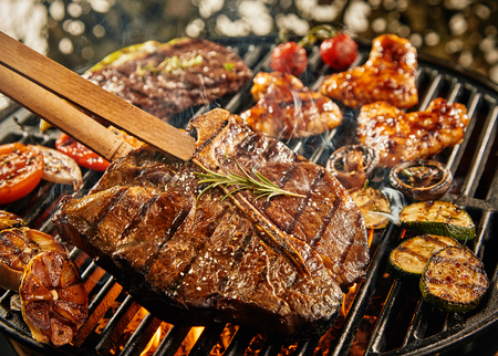 healthy lean t-bone steak grilling on a portable summer BBQ outdoors with assorted meat, garlic, tomatoes, mushrooms, and baby marrow Stock fotó