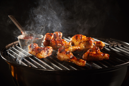 Spicy chicken legs and wings marinated with chili sauce grilling on a smoking fire in a portable barbecue Stock Photo