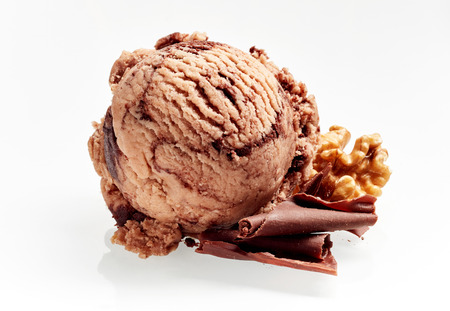 Tasty artisanal Italian walnut ice cream with chocolate flakes and fresh nut ingredients alongside isolated on white
