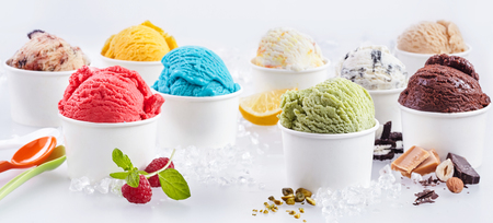 Large selection of artisanal takeaway ice cream in tubs each with the fresh ingredients alongside including raspberry, pistachio, bubblegum, caramel, chocolate, hazelnut and lemon Archivio Fotografico
