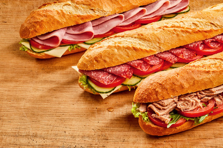 Assorted crusty fresh baguettes with ham, salami and fish fillings on a bed of salad ingredients served on rustic wood with copy space