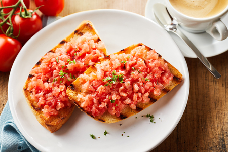 Tomato,garlic and onion salsa on two crunchy fried tostada seasoned wit fresh coriander and served with coffee in an overhead view with tomatoes