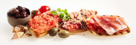 Assorted deep fried tostada with olives, tomato and coriander topped with salsa, tuna, and prosciutto ham over a white panoramic banner background for advertising