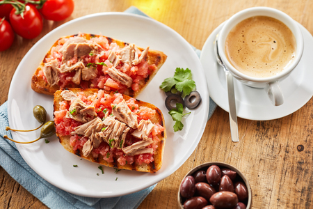 flaked: Healthy lunchtime snack of seafood tostada topped with fresh spicy salsa and flaked tuna and served with a cup of frothy hot cappuccino coffee and black olives
