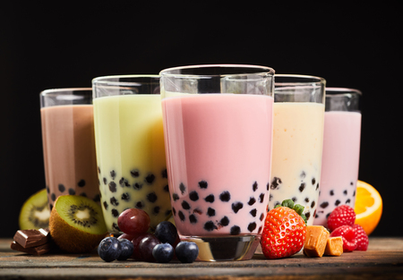 Milky fruit flavored bubble tea with fresh strawberries, grapes, kiwi, raspberry, orange, caramel, and chocolate in a low angle view served in glasses