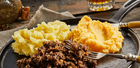 Cooked haggis with neeps and tatties, or mashed potato and turnip served on a metal skillet with a glass of whisky
