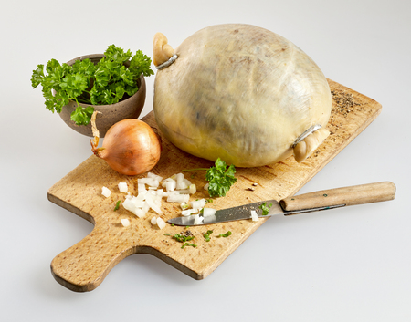 Haggis, herbs and chopped fresh onion on a wooden cutting board preparing a traditional Scottish meal for Robert Burns Supper Stock Photo