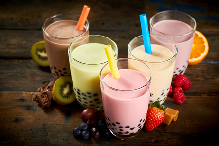 sorts: Selection of bubble tea in a tea house with assorted fruit flavors, caramel and chocolate with fresh ingredients on a wooden table viewed high angle
