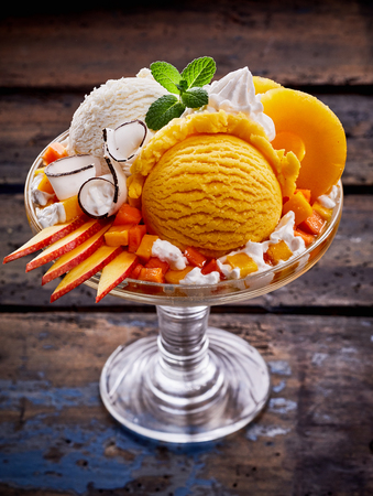 High Angle Close Up View of Sundae Made with Scoops of Vanilla and Peach Flavored Ice Cream, Slices of Fresh Fruit, Whipped Cream and Mint Garnish Served in Glass Dish on Rustic Wood Table Reklamní fotografie