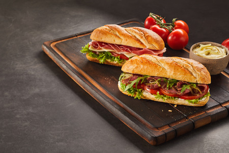 Serving tray with freshly made sandwiches alongside vine ripe tomatoes and dressing cup. Includes copy space.