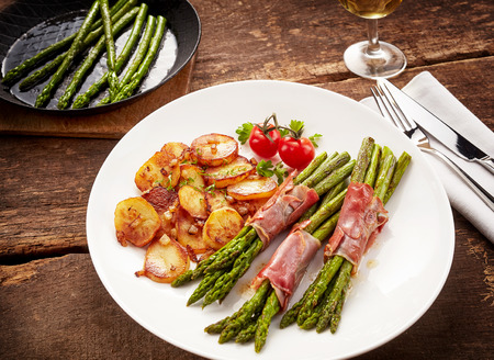 plating: Meal of asparagus, poscuitto and potatoes on plateMeal of asparagus, poscuitto and potatoes on plate with wooden table background