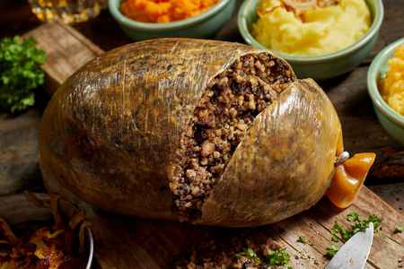 Close up on a sliced open cooked Scottish haggis on a cutting board with side dishes of potato, turnips and carrot, or neeps and tatties 版權商用圖片