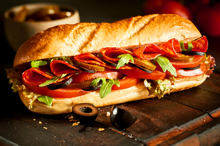 browned: Crusty fresh baguette with salami and salad filling with tomato, lettuce, cucumber, olives and rocket on a rustic board