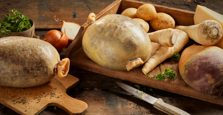 Fresh ingredients for a traditional Scottish haggis meal for Robert Burns Supper with raw turnips, swede, potato, onion and herbs Stock Photo