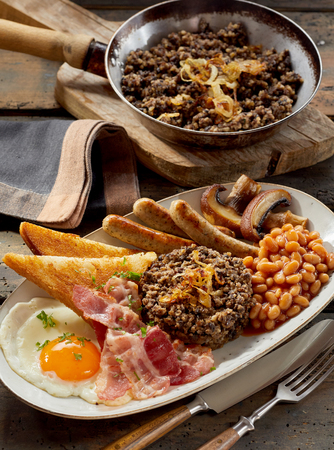 Hearty Scottish breakfast with a slice of haggis served with fried egg, bacon, beans, mushrooms sausages and toast on an oval platter