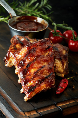 Spicy barbecued marinaded spare ribs from a summer BBQ served on a wooden board with fresh herbs and tomato and a hot cayenne chili pepper