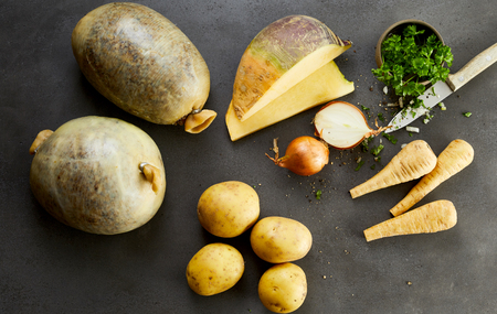 neeps: Ingredients for traditional Scottish haggis, neeps and tatties with fresh potatoes, turnips, rutabaga swede and herbs viewed overhead on dark granite