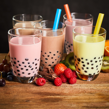 Assortment of milky bubble tea in a tea house with fresh ingredients including strawberries, raspberry , grape, chocolate, kiwi and orange Stock Photo - 75849566