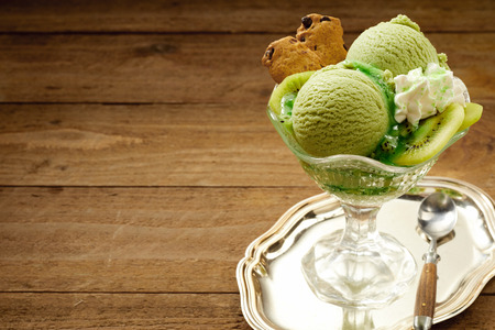 alongside: Tasty creamy Italian kiwifruit ice-cream served with sliced fresh kiwi fruit and whipped cream in a glass dish on a silver tray with copy space alongside on wood