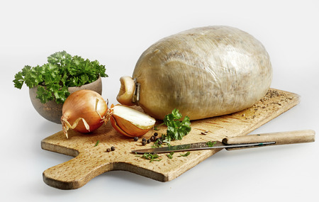 potherb: Prepared uncooked haggis ready for cooking with onion and fresh coriander on a wooden chopping board with kitchen knife
