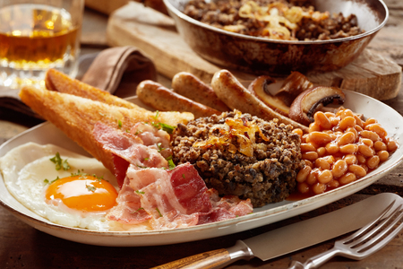 Tasty Scottish haggis breakfast served on an oval platter with whisky to the side with fried egg, mushrooms, bacon, bean and sausage