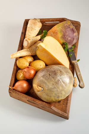Ingredients for haggis with neeps and tatties with fresh onions, swede, turnips, parsley and potatoes together with an uncooked haggis on a wooden tray