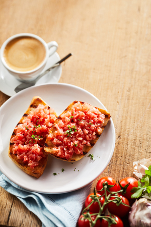 Tomato, garlic, herb and onion salsa on two crispy deep fried tostada or tortilla viewed with the fresh ingredients and coffee from above with copy space