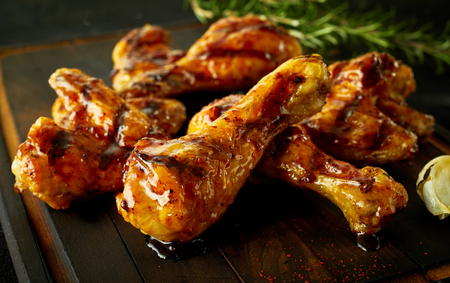 potherb: Delicious crispy spicy chicken legs marinated on a summer barbecue and served on a wooden board as a finger food snack or appetizer