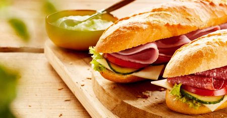 Crusty baguettes with cold ham and salami filling on a bed of fresh salad ingredients served on a wooden board with copy space