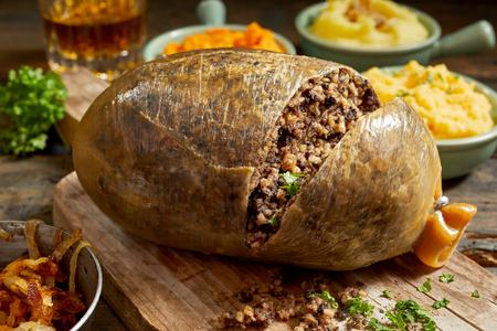 Gesneden opengekookte Schotse haggis die de fijngehakte textuur van het vleesmengsel op een houten bord met bijgerechten van aardappelpuree, raap en wortel met verse kruiden tonen
