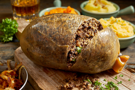 Sliced open cooked Scottish haggis showing the minced texture of the meat mixture on a wooden board with side dishes of mashed potato, turnip and carrot with fresh herbs 版權商用圖片