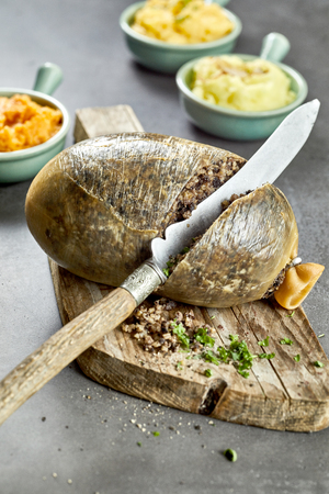 Slicing open a cooked Scottish haggis made with minced liver, hear and lungs stuffed into a sheep stomach with suet, oatmeal onion and seasoning