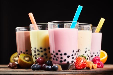 Bicchieri di tè o di bolla di latte rinfrescante con ingredienti di frutta fresca assortiti, caramelle di cioccolato e caramella utilizzate come aromi, vista laterale a basso angolo Archivio Fotografico - 75849697