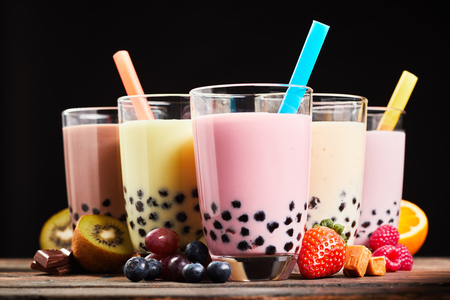 fruit candy: Glasses of refreshing milky boba or bubble tea with assorted fresh fruit ingredients, chocolate and caramel candy used as flavoring, low angle side view Stock Photo