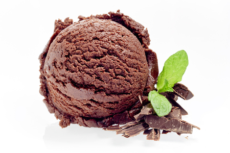 Scoop of gourmet chocolate ice cream with flakes and sprig of fresh peppermint alongside isolated on white