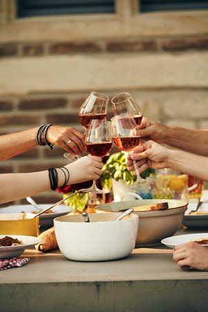 Jonge vrienden rammelende wijnglazen in een toast als ze genieten van een maaltijd van verse lente salade en Italiaanse pasta buiten in de zon Stockfoto