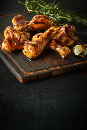 Portion of delicious marinated spicy chicken legs and wings seasoned with fresh rosemary and served on an old wooden board with copy space below