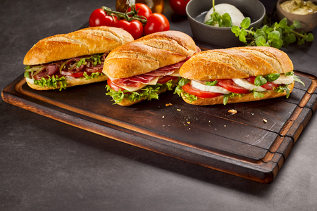 Three ready to eat sandwiches on wooden serving tray with tomatoes and mozzarella cheese ball Reklamní fotografie - 75849707