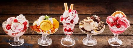 Kleurrijke specialiteit verse tropische fruit en ijsparfait desserts gegarneerd met slagroom in diverse smaken op een rustieke houten achtergrond in een panoramische banner Stockfoto