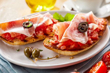 Fried tostada, or tortilla, with fresh spicy tomato, onion and garlic salsa topped with prosciutto ham and olives for a gourmet snack