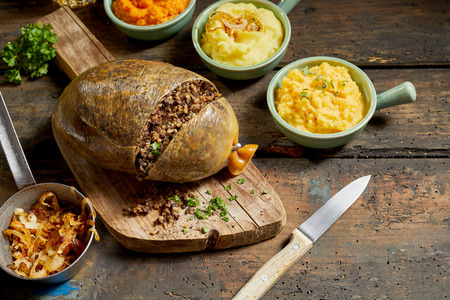 Traditional haggis meal for Robert Burns Supper, a Scottish tradition with cooked sliced haggis, neeps, tatties, onion and carrot on a rustic table Фото со стока