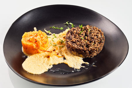 Serving of haggis, neeps and tatties in a restaurant plated on a black plate and garnished with herbs for a traditional Robert Burns Supper
