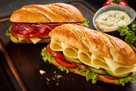 Cheese and pepperoni sandwiches with dressing on side. Crumbs from bread in front of them. Stock Photo