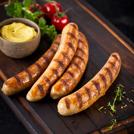 Grilled pork sausages from a summer barbecue served with a dish of mustard herbs and tomato on a wooden cutting board